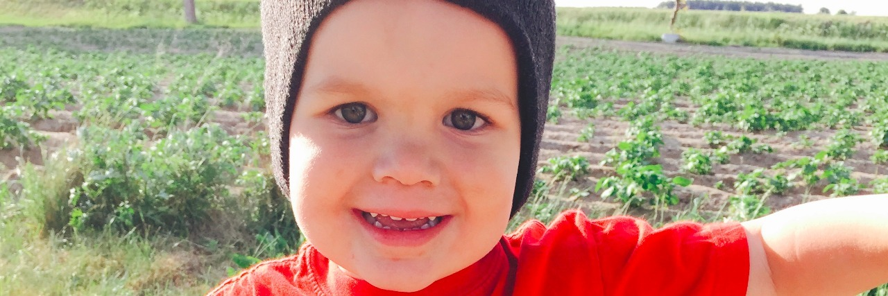 "Little boy wearing a bright orange shirt that reads, ""Alaska"" and a batman beanie-hat on his head"