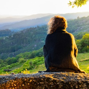 scenic view of woman watching at sunset mountains