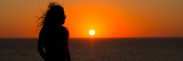 woman in silhouette looking at orange sunset