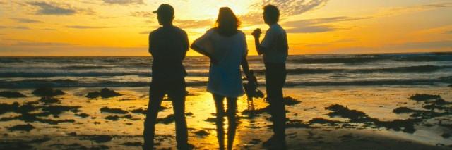 Friends watching sunset on beach