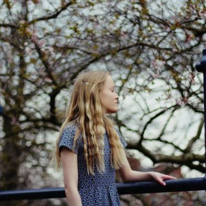 girl surrounded by trees looking towards something