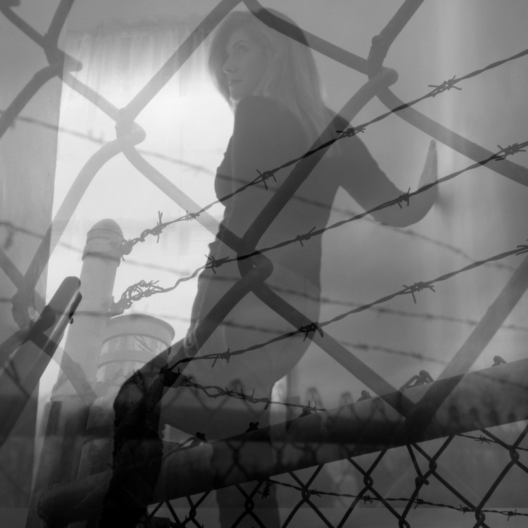 a double exposure image of a woman against a fence