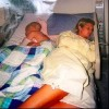 woman and young boy asleep together in hospital bed