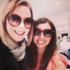 Two female friends wearing sunglasses, smiling at camera.