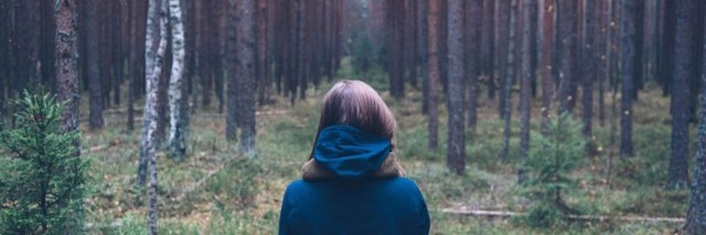 woman wearing blue jacket and facing a forest