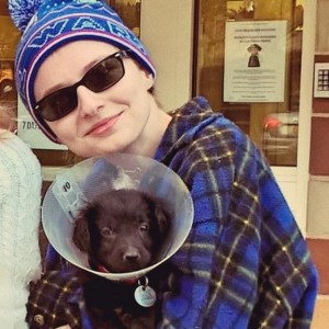 woman holding dog with cone on head
