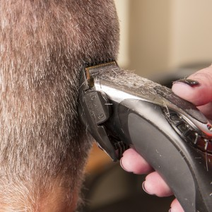 hand using electric clippers to shave head