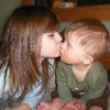 Little girl kissing a baby boy with Down syndrome