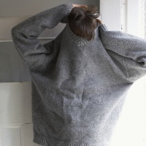 Woman pulling sweater over head