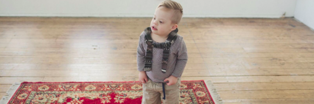 Boy wearing a backpack, standing on carpet at home
