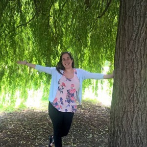 young woman standing next to a tree with her arms out