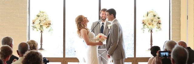 husband and wife standing at the altar getting married and laughing