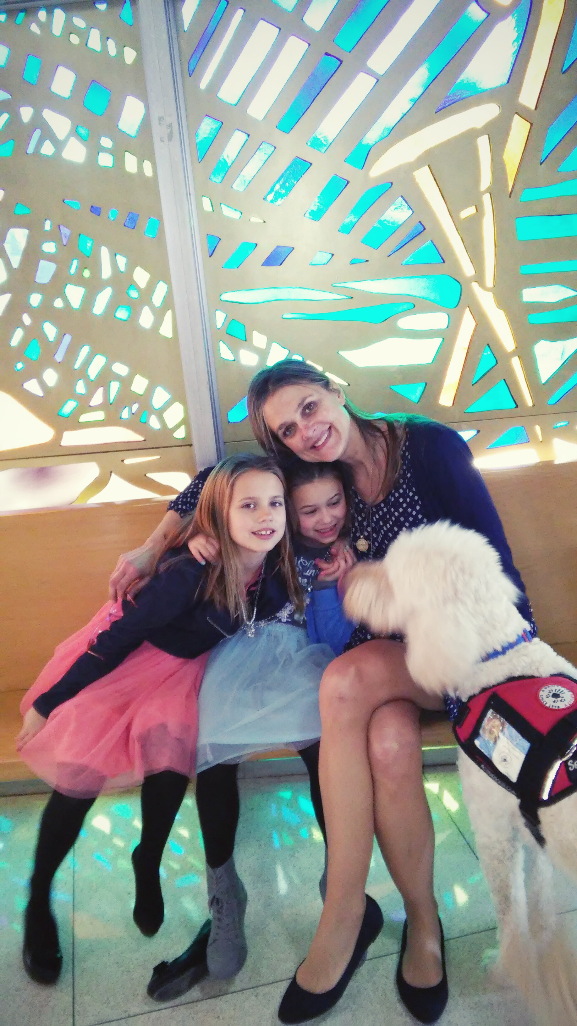 Mom and two girls sitting with service dog