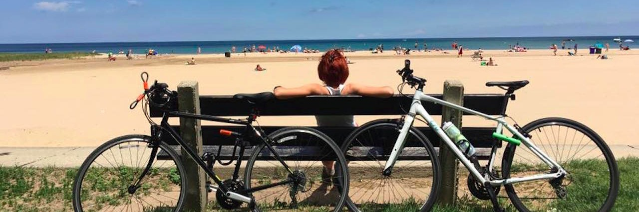 woman sitting on a bench looking at the beach with bikes behind her.