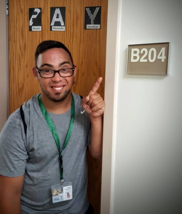 boy with down syndrome standing outside college dorm door