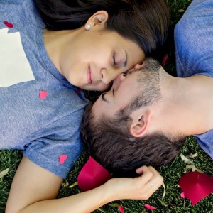 A young man and woman in-love, laying on the grass.