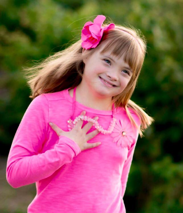 girl with down syndrome wearing pink shirt