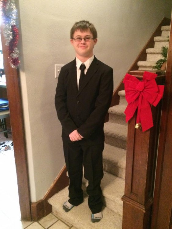 boy with down syndrome wearing a suit and standing at bottom of stairs
