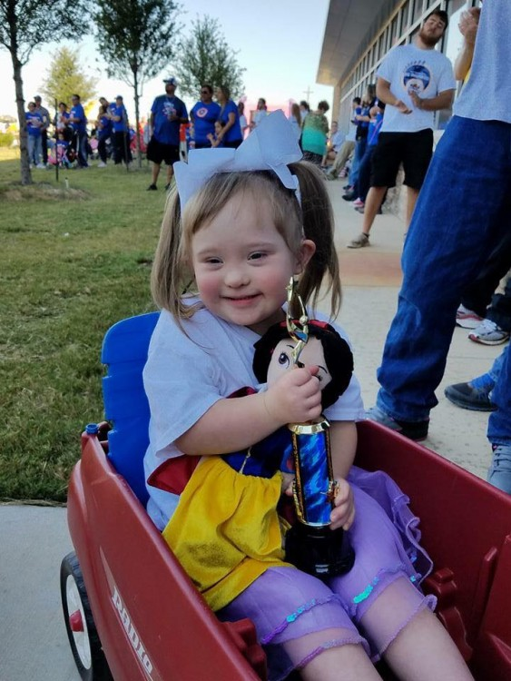 girl with down syndrome sitting in wagon holding doll