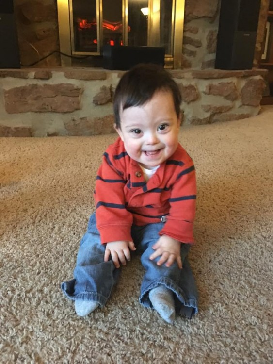 little boy with down syndrome sitting on carpet