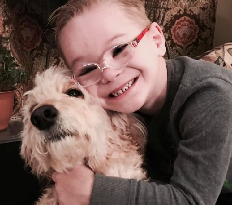 boy with down syndrome hugging dog