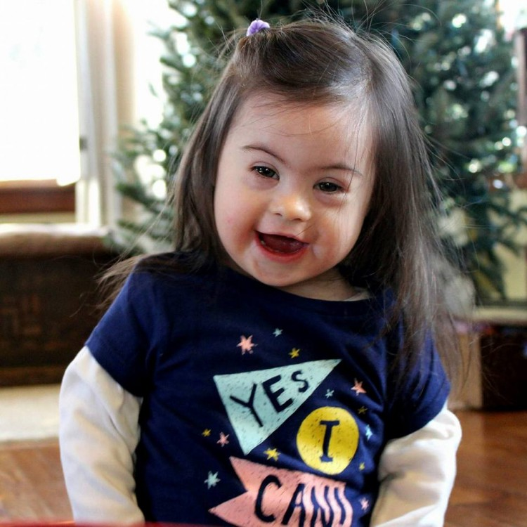 little girl with down syndrome standing in front of christmas tree