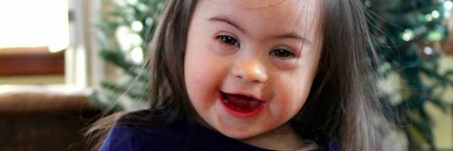 little girl with down syndrome in front of christmas tree