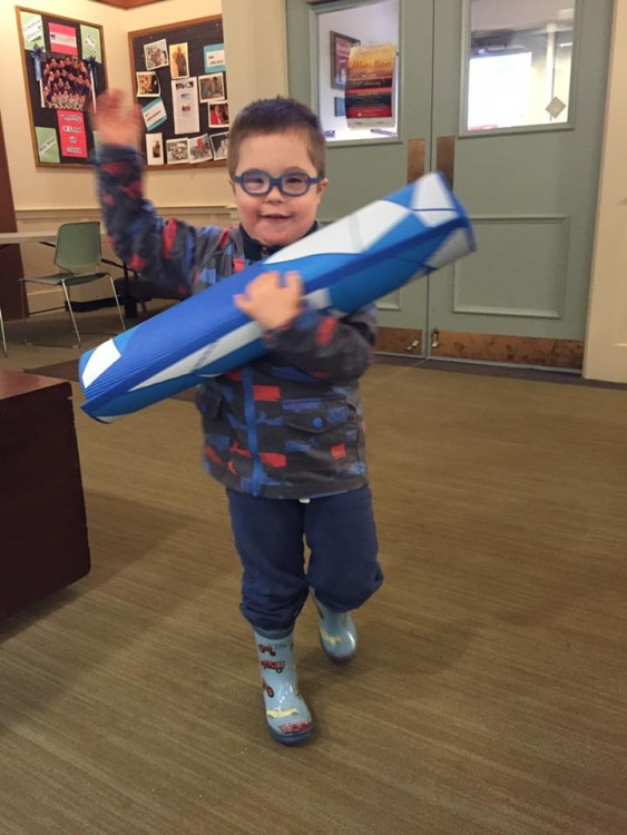 boy with down syndrome carrying yoga mat