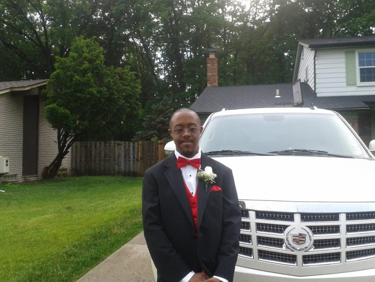 man with down syndrome wearing formal suit standing next to car