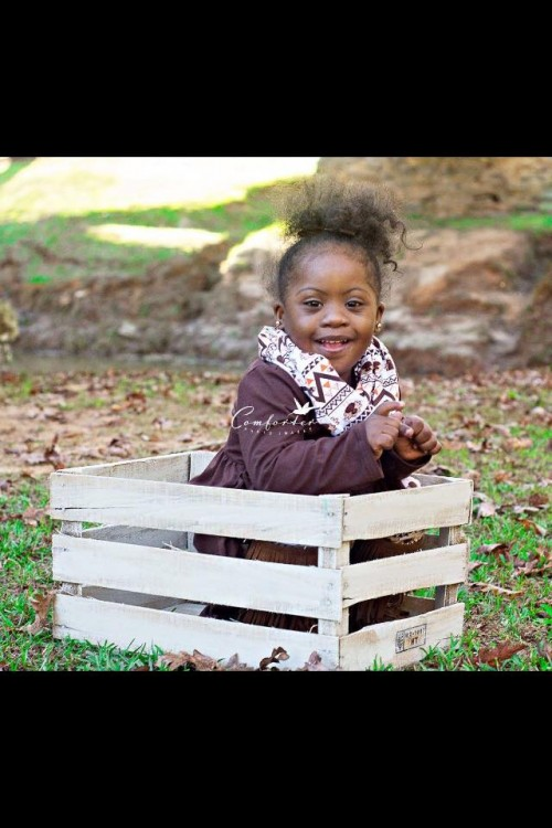 girl with down syndrome sitting outside under tree