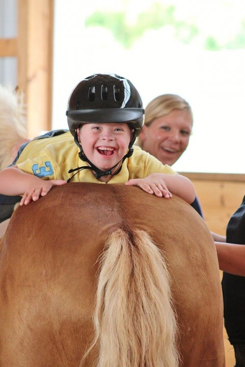 boy with down syndrome riding a horse