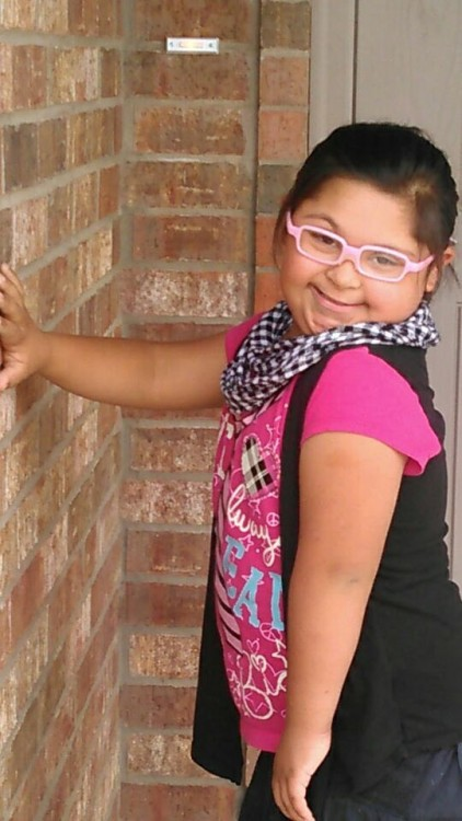 girl with down syndrome wearing pink glasses