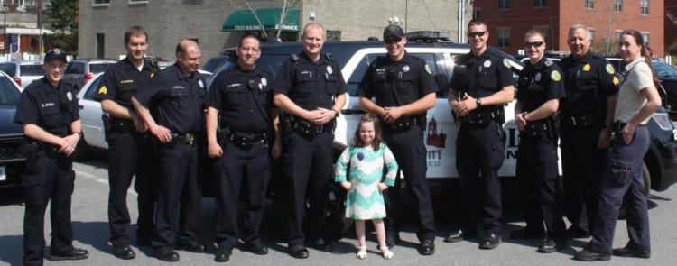 girl with down syndrome standing with police officers