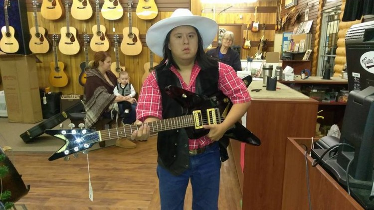 man with down syndrome playing guitar in guitar store