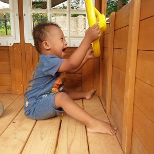 Little boy with Down syndrome playing with a yellow pirate wheel in a playset