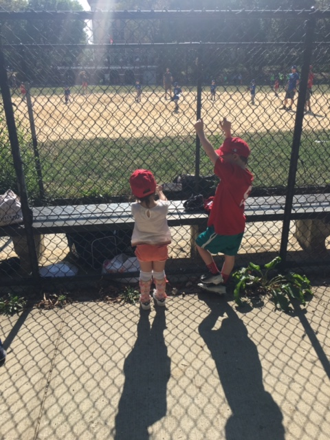 two young kids standing behind fence at baseball field
