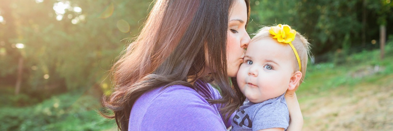 Mom holding baby daughter, kissing her cheek in front of a tree
