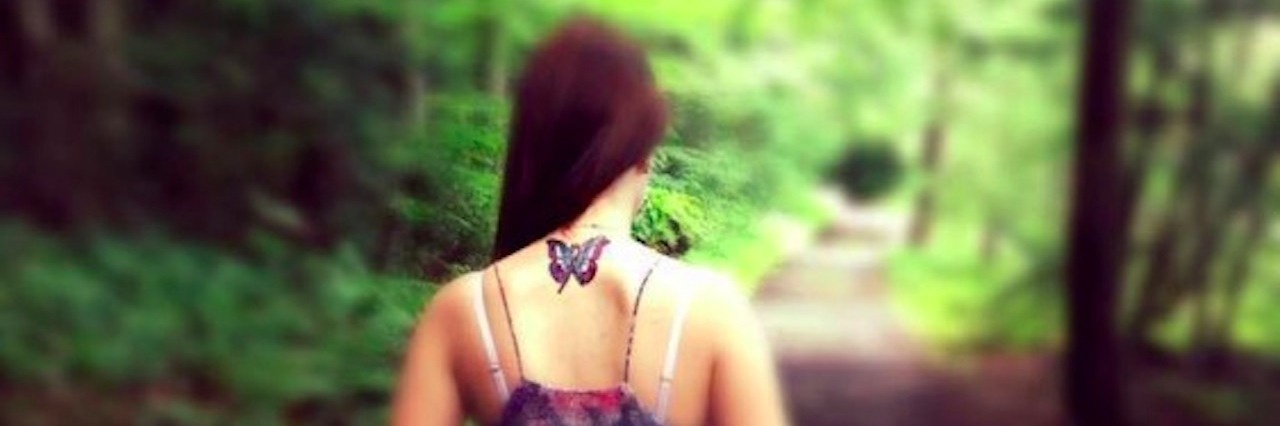 A woman hiking, with a butterfly tattoo on her neck.
