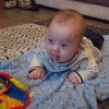 A baby boy with Down syndrome lying on the floor on top of a blue blanket during tummy time