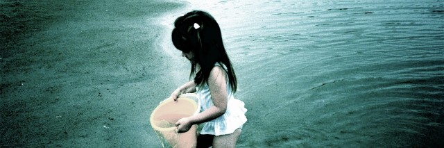 young girl holding a bucket and standing in shallow water