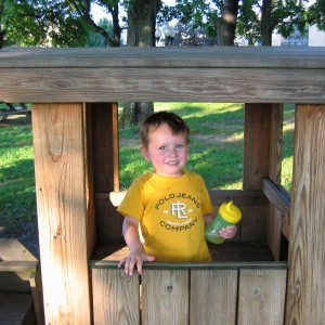 Boy wearing yellow shirt and holding a sippy cup with a matching yellow top playing inside a wooden play structure.