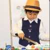 A boy wearing a tan colored hat, white shirt and blue vest cutting his birthday cake.