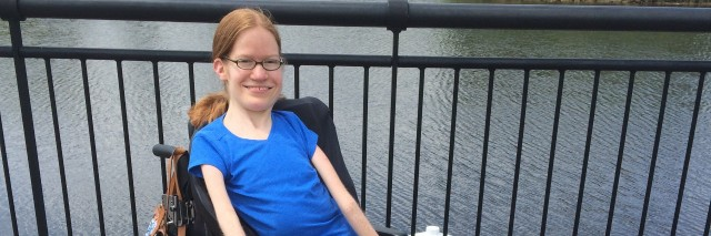Laura Robb, young woman in a blue power wheelchair sitting outdoors near a lake..