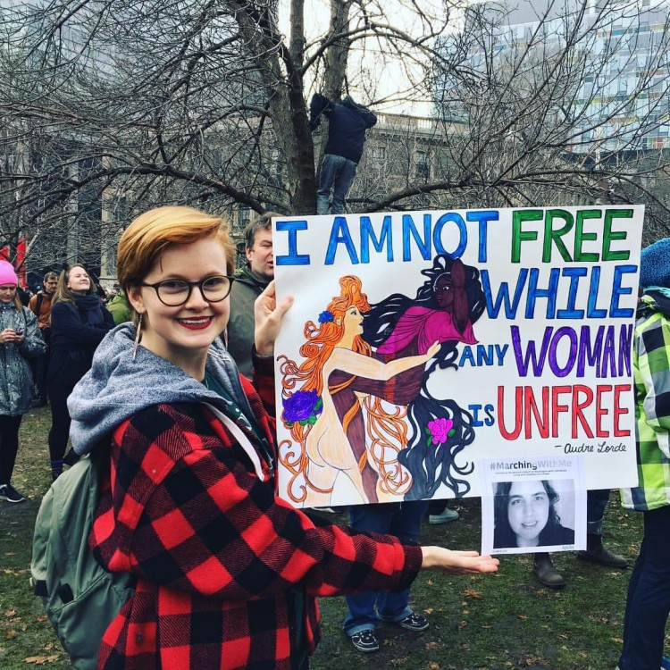 woman holding a sign that says i am not free while any woman is unfree
