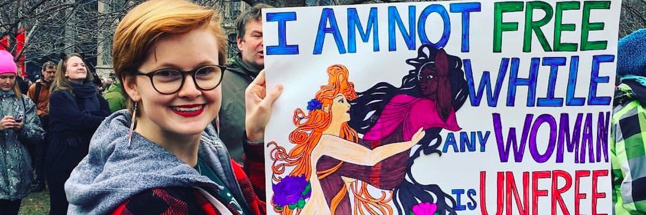 woman carrying sign that says i am not free while any woman is unfree