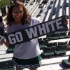 college girl holding a banner that reads 'go white' and standing in the bleachers at a football game