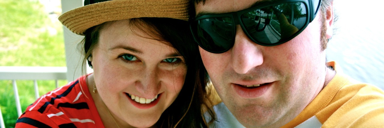 man in sunglasses and woman in a hat smiling