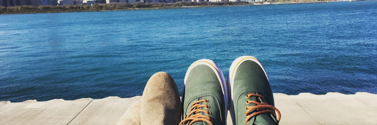 A man and woman's feet, facing a body of water and a city skyscraper.