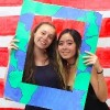 two college girls holding a large frame around their heads
