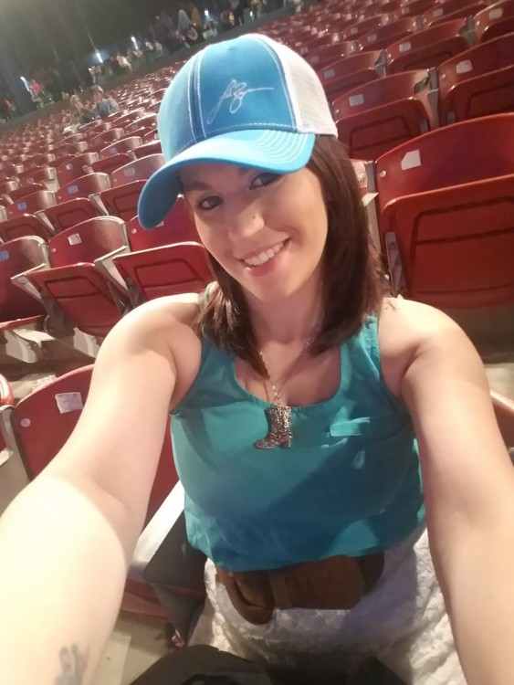 Woman wearing a baseball hat, waiting for a concert to begin.